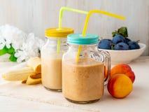 De nectarine van de banaanperzik smoothie in twee kruiken, vers fruitmilksha stock foto