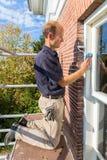 De Nederlandse schilder op steiger maakt raamkozijn met doek schoon royalty-vrije stock foto
