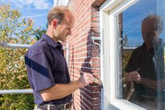 De Nederlandse schilder schildert raamkozijn met borstel stock afbeeldingen