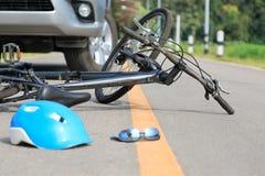 De neerstorting van de ongevallenauto met fiets op weg stock foto