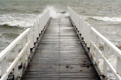 De neerstortingen van de golf langs een pier Royalty-vrije Stock Afbeeldingen