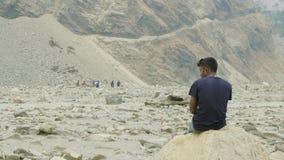 De Nepalese gids heeft een rust op de steen Trek van de Manaslukring stock videobeelden