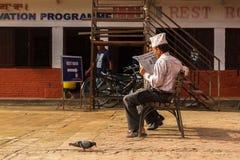 De Nepalese mens leest een krant in Katmandu, Nepal Stock Afbeelding