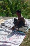 De Nepalese mens puft omhoog hoofdkussen neer Stock Foto's