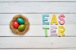 De nestkroon, eieren, Pasen vouwde document origami het kleurrijke van letters voorzien op witte houten planken rustieke achtergr Stock Fotografie