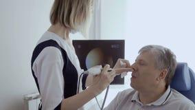 De neus van de artsencontrole van bejaarde met ENT telescoop stock footage