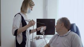 De neus van de artsencontrole van de hogere mens met ENT telescoop stock videobeelden