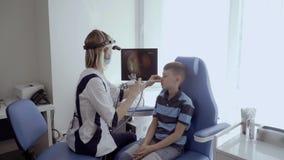 De neus van de artsencontrole van jongen met ENT telescoop stock video