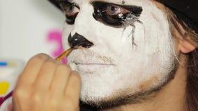 De Neuszwarte van kunstenaarshand painting man in Halloween stock videobeelden