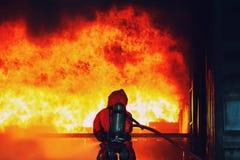 De nevel van het brandbestrijderswater met hoge druk aan brandrand met beschadigd huis, goedang Brandbestrijdersstrijd met de bra stock afbeeldingen