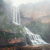 De nevelige watervallen tuimelen onderaan klippen stock fotografie