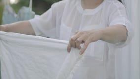 De niet erkende rijpe rieten mand van de vrouwenholding terwijl in openlucht het hangen van witte kleren op een drooglijn washday stock video