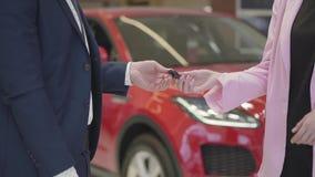 De niet erkende verkoper verzendt de sleutels naar de nieuwe auto aan de nieuwe eigenaar Een mens in een pak ging een overeenkoms stock footage