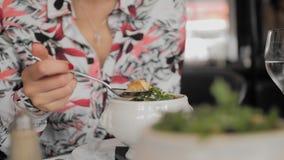 De niet erkende vrouwelijke toerist eet traditionele soep met croutons, gesmolten kaas en greens in een restaurant van Parijs Han stock videobeelden