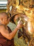De niet geïdentificeerde Birmaanse monnik maakt het standbeeld van Boedha met het gouden document bij de tempel van Mahamuni Boed Royalty-vrije Stock Foto