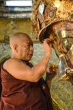 De niet geïdentificeerde Birmaanse monnik maakt het standbeeld van Boedha met het gouden document bij de tempel van Mahamuni Boed Stock Foto