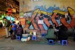 De niet geïdentificeerde de jeugdmensen eten bij de verkopers van het straatvoedsel in het Oude Kwart van Hanoi bij nacht Royalty-vrije Stock Foto's