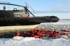 De niet geïdentificeerde die toeristen met een ijs van het overlevingskostuum worden opgevoerd zwemmen in bevroren Oostzee Royalty-vrije Stock Foto