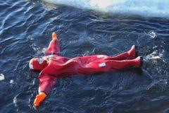 De niet geïdentificeerde die toeristen met een ijs van het overlevingskostuum worden opgevoerd zwemmen in bevroren Oostzee Stock Fotografie