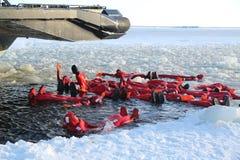 De niet geïdentificeerde die toeristen met een ijs van het overlevingskostuum worden opgevoerd zwemmen in bevroren Oostzee Stock Foto's