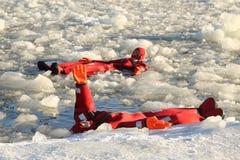 De niet geïdentificeerde die toeristen met een ijs van het overlevingskostuum worden opgevoerd zwemmen in bevroren Oostzee Stock Afbeelding