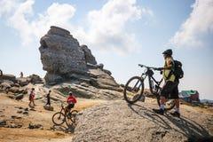 De niet geïdentificeerde groep fietsers beklimt de heuvel in Bucegi-Bergen in Roemenië stock foto's