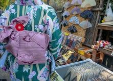 De niet geïdentificeerde Japanse dame droeg groene kimono winkelend voor goed in Arashiyama stock foto's