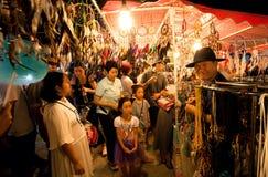 De niet geïdentificeerde kinderen en de families die rond Thaise nachtmarkt lopen met windvangers winkelen stock afbeeldingen