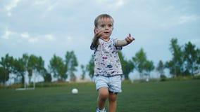 De niet geïdentificeerde kinderen spelen voetbal op de achtergrond van zonsondergang Langzame Motie stock footage
