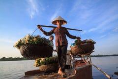 De niet geïdentificeerde landbouwers dragen bloemen aan de markt Stock Foto