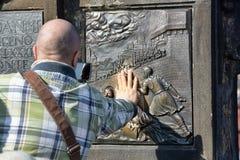 De niet geïdentificeerde mens raakt zijn hand aan de bas-hulp op Charles Bridge, maakt een wens Royalty-vrije Stock Afbeeldingen