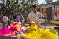 De niet geïdentificeerde mens verkoopt gepoederde kleurstoffen die voor Holi-festival in India worden gebruikt Stock Afbeelding