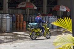 De niet geïdentificeerde mensen draagt gasfles in motorfietsen Royalty-vrije Stock Foto's