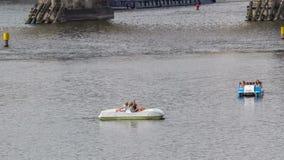 De niet geïdentificeerde mensen genieten van een cruise op een pedaalboot in Vltava-rivier timelapse hyperlapse in Praag, Tsjechi stock video