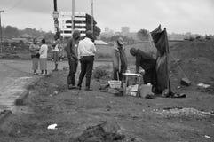De niet geïdentificeerde mensen lopen in modder stock afbeeldingen