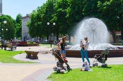 De niet geïdentificeerde mensen ontspannen bij fontein in park, Victory Sq Stock Foto