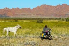 De niet geïdentificeerde Mongoolse herder berijdt motor stock afbeeldingen