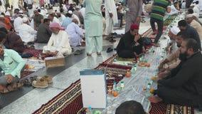 De niet geïdentificeerde Moslimmensen treffen om snel bij dageraad buiten Nabawi-moskee in Medina, Saudi-Arabië te breken voorber stock video