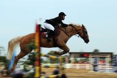 De niet geïdentificeerde ruiterruiter van het motieonduidelijke beeld sprongpaard proberend toont om hindernissen bij de sport van Royalty-vrije Stock Foto