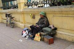 De niet geïdentificeerde schoenpoetsen oude mens zit op de straat, wachtend op cliënten Stock Afbeelding