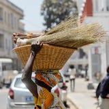 De niet geïdentificeerde Senegalese vrouw draagt een mand met bezems in t royalty-vrije stock afbeelding