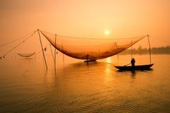 De niet geïdentificeerde visser controleert zijn netten in vroege ochtend op rivier in Hoian, Vietnam stock afbeeldingen