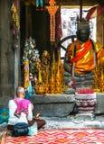 De niet geïdentificeerde vrouw bidt dichtbij boeddhistisch altaar Stock Fotografie