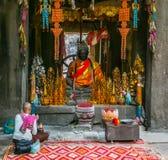De niet geïdentificeerde vrouw bidt dichtbij boeddhistisch altaar Royalty-vrije Stock Foto's