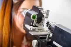 De niet geïdentificeerde vrouw controleert visie door modern materiaal, ogenexamen in optisch, op een vage achtergrond stock afbeeldingen