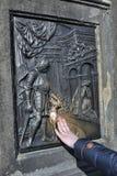 De niet geïdentificeerde vrouw raakt zijn hand aan de bas-hulp op Charles Bridge, maakt een wens Stock Afbeelding