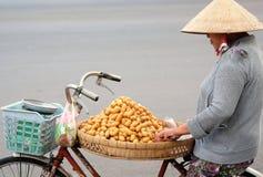 De niet geïdentificeerde vrouw verkoopt voedsel en vruchten op de straat, Mekong deltagebied, Vietnam Stock Foto's