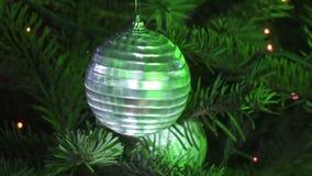 De nieuwe bal van de jaarspiegel tegen de achtergrond van verfraaid met een slinger van een Kerstboom stock video