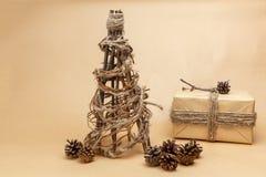 De nieuwe die hand van de jaarboom - in ecostijl wordt gemaakt met gift in document wordt ingepakt en pinecones Royalty-vrije Stock Foto's