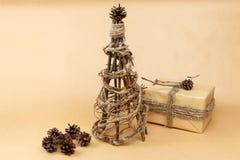 De nieuwe die hand van de jaarboom - in ecostijl wordt gemaakt met gift in document wordt ingepakt en pinecones Royalty-vrije Stock Fotografie
